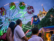 "27 NOVEMBER 2012 - BANGKOK, THAILAND: A ferris wheel spins in front of Wat Saket during the temple fair in Bangkok. Wat Saket, popularly known as the Golden Mount or ""Phu Khao Thong,"" is one of the most popular and oldest Buddhist temples in Bangkok. It dates to the Ayutthaya period (roughly 1350-1767 AD) and was renovated extensively when the Siamese fled Ayutthaya and established their new capitol in Bangkok. The temple holds an annual fair in November, the week of the full moon. It's one of the most popular temple fairs in Bangkok. The fair draws people from across Bangkok and spills out in the streets around the temple.    PHOTO BY JACK KURTZ"