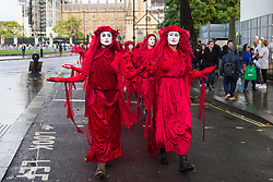 London, UK. 8 October, 2019. Climate activists from Extinction Rebellion's Red Brigade walk through Westminster on the second day of International Rebellion protests to demand a government declaration of a climate and ecological emergency, a commitment to halting biodiversity loss and net zero carbon emissions by 2025 and for the government to create and be led by the decisions of a Citizens' Assembly on climate and ecological justice.