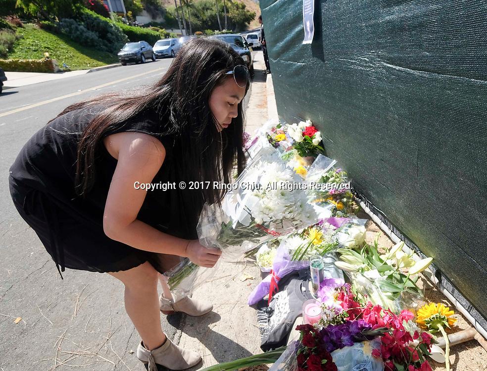 7月21日,在美国洛杉矶帕洛斯弗迪斯庄园,一名粉丝把鲜花摆放在林肯公园&rdquo;乐队主唱切斯特&middot;本宁顿屋外。美国警方20日证实,著名摇滚乐队&ldquo;林肯公园&rdquo;的主唱切斯特&middot;本宁顿当天在洛杉矶家中疑似自杀身亡,终年41岁。新华社发 (赵汉荣摄)<br /> A fan places flowers at a memorial site outside of Chester Bennington's home of  in Palos Verdes Estates, California, the United States, on Friday, July 21, 2017. Chester Bennington, lead singer of alt-rock band Linkin Park, was found dead on Thursday morning in his Palos Verdes Estates home of an apparent suicide. He was 41.(Xinhua/Zhao Hanrong)(Photo by Ringo Chiu)<br /> <br /> Usage Notes: This content is intended for editorial use only. For other uses, additional clearances may be required.