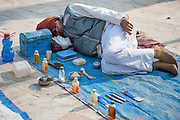 Indian street barber sleeping on the floor with his tools (India)