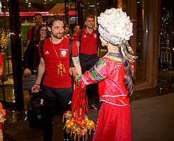 NANNING, CHINA - Monday, March 19, 2018: Wales' Joe Allen is greeted by a woman in traditional costume as the team arrive at the Wanda Realm Resort in Nanning for the 2018 Gree China Cup International Football Championship. (Pic by David Rawcliffe/Propaganda)