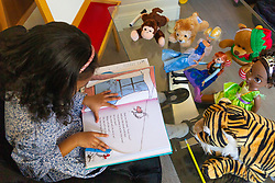 Four-year-old Alannah George reads Dr Seuss's The Cat In The Hat for her attentive audience of toys. She has an IQ of 140 and taught herself to read at two-and-a-half and is a member of Mensa. Iver, Buckinghamshire, March 10 2019.