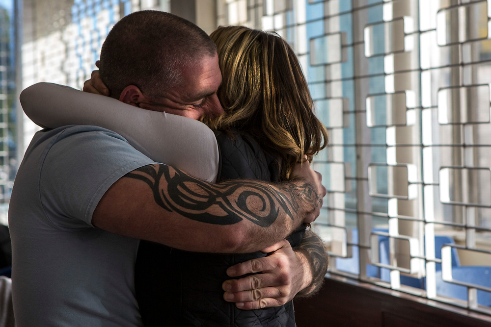 A prisoner embraces his wife at the start of a visit. HMP/YOI Portland, Dorset, United Kingdom.