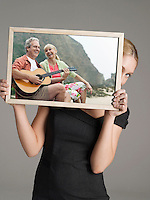 Young businesswoman peeking from behind photograph of happy couple with guitar on vacation against gray background