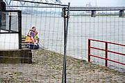 Nederland, Nijmegen, 21-6-2012De damwand die de Waalkade tegenhoudt is aan het verzakken, werken. Afgelopen week is gebleken dat deze waterkering ondergraven wordt door wegspelend zand. Hij is enkele centimeters uit positie en dus instabiel. De kade is afgezet en er mogen geen schepen aanlegen. Rode vlag. De horeca is ernstig gedupeerd omdat veel terrassen nu achter een hek liggen en de mensen er niet gaan zitten. Het zal ook gevolgen hebben voor de 4daagse en de zomerfeesten.Specialisten van de gemeente onderzoeken de kade.De waterkering dateerd van 1980, 1981.Foto: Flip Franssen/Hollandse Hoogte