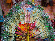 "04 APRIL 2015 - CHIANG MAI, CHIANG MAI, THAILAND: Money donated to a Tai boy being ordained at the Poi Sang Long at Wat Pa Pao in Chiang Mai. The Poi Sang Long Festival (also called Poy Sang Long) is an ordination ceremony for Tai (also and commonly called Shan, though they prefer Tai) boys in the Shan State of Myanmar (Burma) and in Shan communities in western Thailand. Most Tai boys go into the monastery as novice monks at some point between the ages of seven and fourteen. This year seven boys were ordained at the Poi Sang Long ceremony at Wat Pa Pao in Chiang Mai. Poy Song Long is Tai (Shan) for ""Festival of the Jewel (or Crystal) Sons.      PHOTO BY JACK KURTZ"