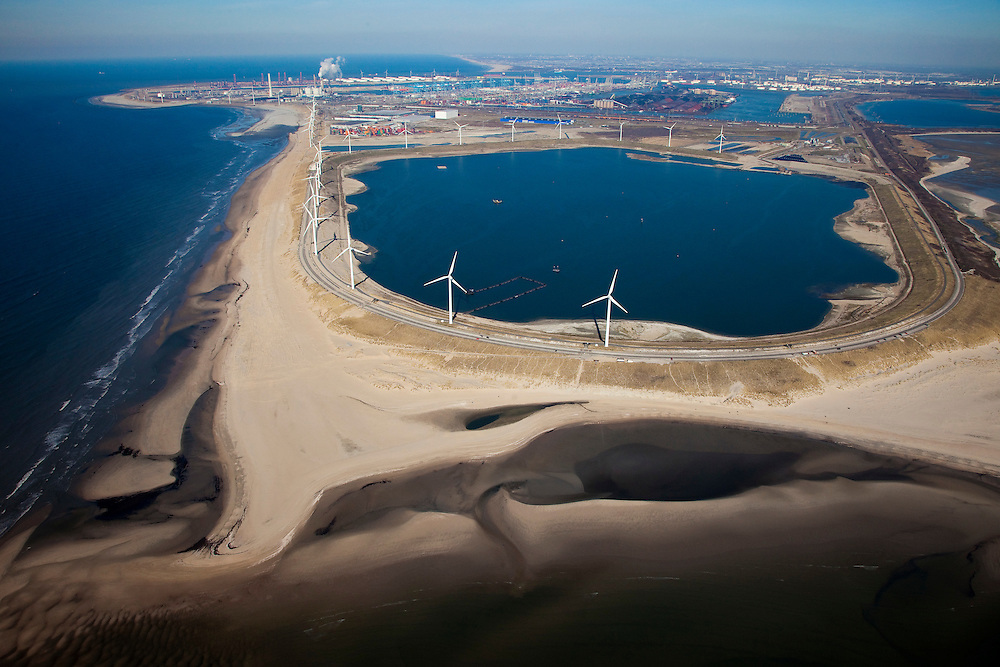 Nederland, Rotterdam, Maasvlakte, 20-03-2009; De Slufter, grootschalige opslagplaats voor vervuild havenslib. De verontreinigde baggerspecie komt voort uit het onderhoudsbaggerwerk in de Rotterdamse haven waarbij de haven op diepte wordt gehouden. Langs de rand van de Slufter zijn windmolens gebouwd en in de Noordzee, direkt links naast het depot, wordt de Tweede Maasvlakte aangelegd. Links aan de horizon de poederkoolgestookte elektricitieitscentrale van E.ON (EON), in het midden aan de verre horizon de kust van Delfland. Slufterstrand (Strand Slufter) in de voorgrond. The Slufter area in the South-West of the Netherlands, large-scale depot of contaminated harbor sludge from the Port of Rotterdam . Along the edge of the Slufter windmills are built in the North Sea, immediately at the left side of the depot, the Second Maasvlakte will be constructed. Top left the powdered coal-fired power plant of E. ON (EON)...Swart collectie, luchtfoto (toeslag); Swart Collection, aerial photo (additional fee required); .foto Siebe Swart / photo Siebe Swart