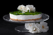 Mojito cake with mint and rum decorated with roses, on black background.