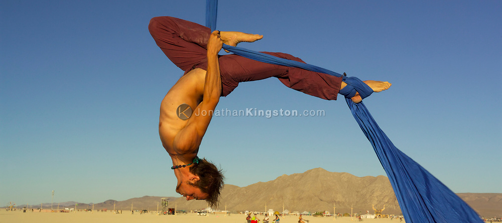 BLACK ROCK CITY, NV:  A man from the Boston dance group Fire Fly Dance demonstrates some aerial dance for the residents of Black Rock City, Nevada.