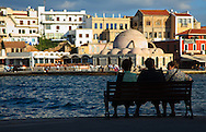 Old ladies sit and gossip on a bech in the Port of Chania.