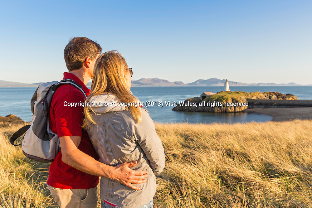 Couple looking out over beach and lighthouse <br /> Llanddwyn Island<br /> Near Newborough<br /> Anglesey<br /> North<br /> Walking<br /> Activities and Sports