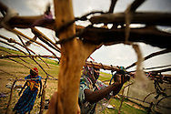 Women build a shelter of sticks and swaths of cloth in Abougoudam, a village in a remote area of Eastern Chad.