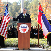 Adam Robison | BUY AT PHOTOS.DJOURNAL.COM<br /> Speaker of the House Phillip Gunn, address those in attedance at Wednesday mornings Veterans Day ceremony at Veterans Park in Tupelo. Tupelo High School ninth graders and choir members, Elizabeth Middleton and Kate Burleson, hold the flags due to the windy morning.
