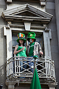 Couple watch the Dublin, St. Patrick's Day parade from balcony on O'Connell Street, Dublin