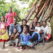 CAPTION: Christopher Onyimo has a large family. He and his wife (not pictured here because she has gone away to study) have seven children. In this picture, Christopher poses with his daughter-in-law, some of his children and grandchildren. LOCATION: Apapai Parish, Otuboi Sub-county, Kalaki County, Kaberamaido District, Uganda. INDIVIDUAL(S) PHOTOGRAPHED: From left to right: Unknown, Anthony Oryokot, Christopher Onyimo, Kenneth Onyimo, Rebecca Aniko, unknown, unknown, unknown and Vicky Atimo.