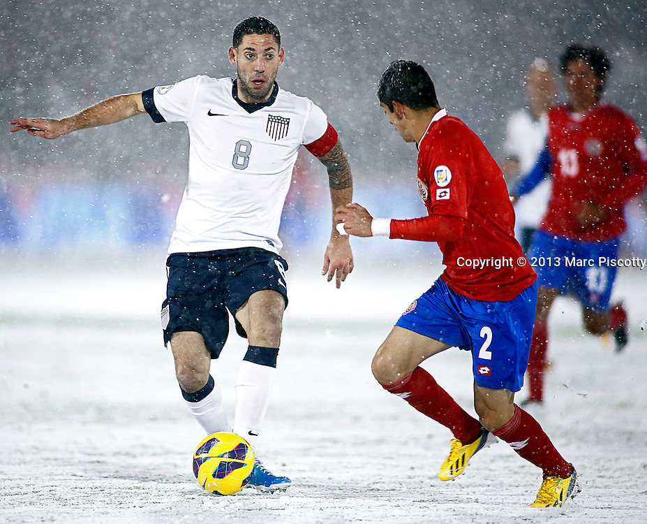 SHOT 3/22/13 7:22:54 PM - United States forward Clint Dempsey #8 looks to pass in front of Costa Rica's Christian Gamboa #2 during their World Cup qualifying game at Dick's Sporting Goods Park in Commerce City, Co. on Friday March 22, 2013. The U.S. won the game 1-0 in a spring blizzard that blanketed the pitch and stadium in snow. (Photo by Marc Piscotty / © 2013).