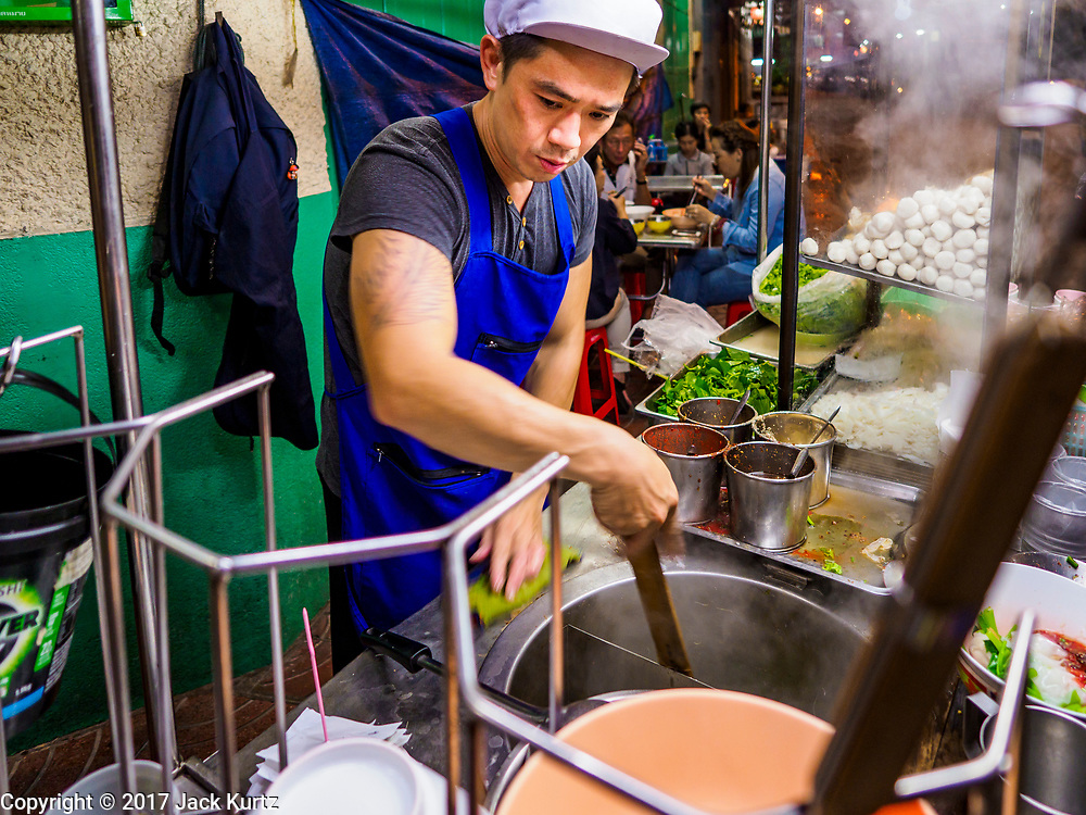 "18 MAY 2017 - BANGKOK, THAILAND:  A chef makes noodle soups for customers at a street food stall in Bangkok's Chinatown. City officials in Bangkok have taken steps to rein in street food vendors. The steps were originally reported as a ""ban"" on street food, but after an uproar in local and international news outlets, city officials said street food vendors wouldn't be banned but would be regulated, undergo health inspections and be restricted to certain hours on major streets. On Yaowarat Road, in the heart of Bangkok's touristy Chinatown, the city has closed some traffic lanes to facilitate the vendors. But in other parts of the city, the vendors have been moved off of major streets and sidewalks.     PHOTO BY JACK KURTZ"