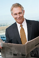 Businessman reading newspaper by window