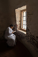 Portrait of a girl reading by the light of a window.