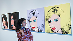 "© Licensed to London News Pictures. 10/03/2020. LONDON, UK. A staff member poses next to (L to R) ""Mick Jagger"", and ""Debbie Harry"", 1980, both by Andy Warhol. Preview of ""Andy Warhol"", a retrospective of over 100 works by one of the most recognisable artists of the late 20th century.  The exhibition runs 12 March to 6 September 2020 at Tate Modern.  Photo credit: Stephen Chung/LNP"