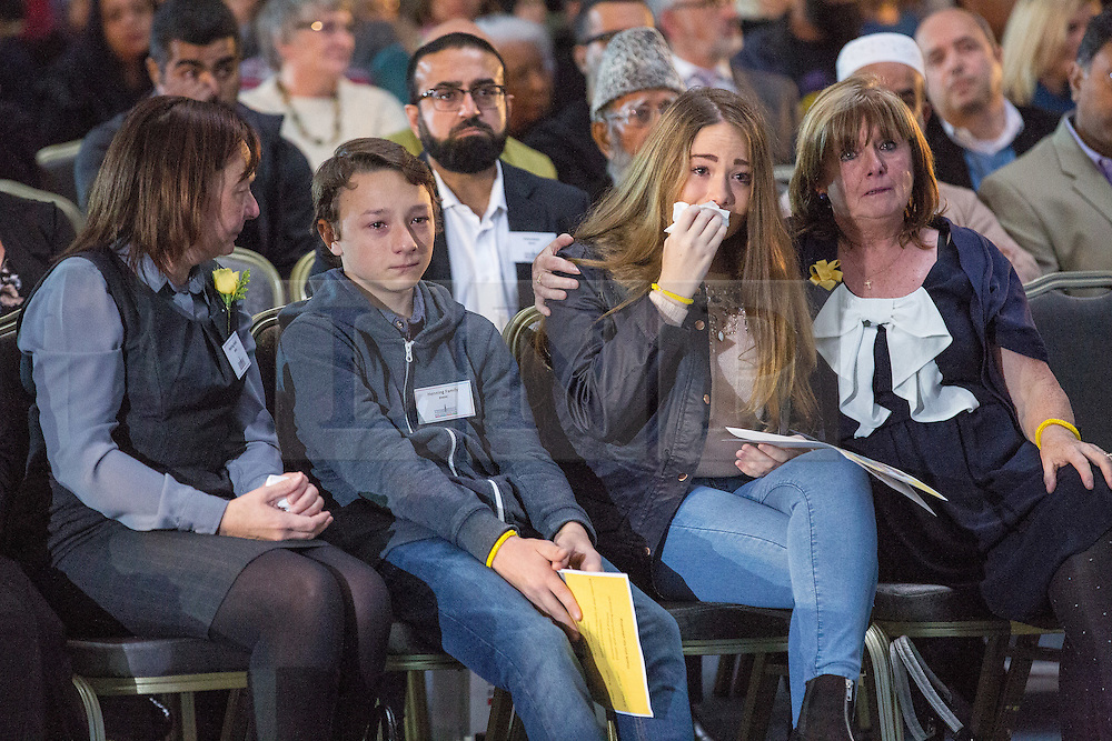 © Licensed to London News Pictures . 12/10/2014 . Manchester , UK . Members of Alan Henning's family - his wife , son and daughter - watch as a short tribute film in played at an interdenominational memorial service in memory of the murdered British aid worker , Alan Henning , hosted at the British Muslim Heritage Centre in Manchester . Photo credit : Joel Goodman/LNP