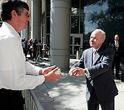 Former Enron chairman Kenneth Lay (R) returns a ball he signed to supporter Steve Schares outside the Bob Casey U.S. Courthouse following proceedings in his fraud and conspiracy trial, May 16, 2006, in Houston. The defense presented it's closing arguments in the trial that has spanned 16 weeks. (Photo by Dave Einsel)