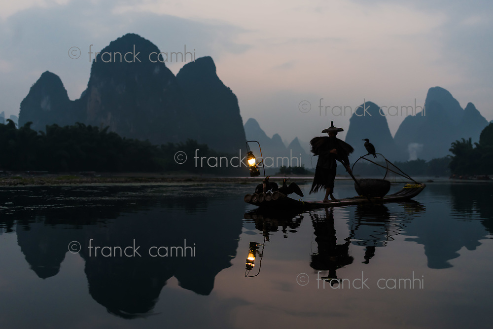 Yangshuo , China - September 29 , 2014 : fisherman fishing  with cormorant Li river, between Guilin and Yangshuo in Guangxi province  China