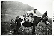 man trying to sit on a donkey with mountain in background