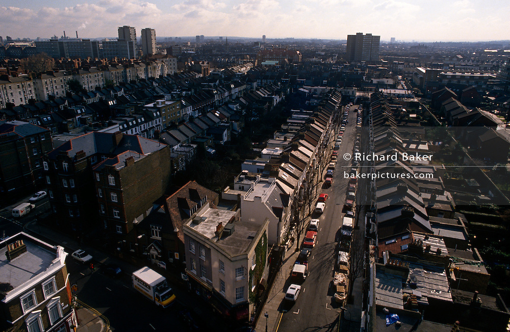 An aerial view of a west London street and its surrounding neighbourhood. Homes and houses, flats, tower blocks and estates are seen stretching into the distance from this high vantage-point across the capital city. Cars of residents are parked on both sides of the tree-lined roads.