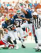 Green Bay Packers defensive lineman Tim Harris (97) celebrates with Detroit Lions linebacker Chris Spielman (54) as Philadelphia Eagles defensive end Reggie White (92) looks on after Harris recovers a fumble during the 1990 NFL Pro Bowl football game between the AFC American Football Conference and the NFC National Football Conference on Feb. 4, 1990 in Honolulu. The NFC won the game 27-21. (©Paul Anthony Spinelli)