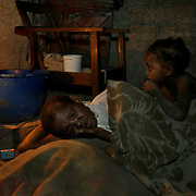Meamui Wanalu, who doesn't know her age, prepares for bed on the floor of her hut with rag stuffed food sacks for pillows as her 6-year-old granddaughter comes to join her. Wanalu raises 4 grandchildren, two of which are HIV positive, and on ART. She lives in a decrepit hut that a villager lets her use and relies on World Food Program rations and charity from neighbors to care for her orphans. The World Food Program provides nutritional support to the ART program, but the rations are scheduled to run out at the end of April, unless donors come through with money to buy food locally or find another way of getting food to Zambia quickly.