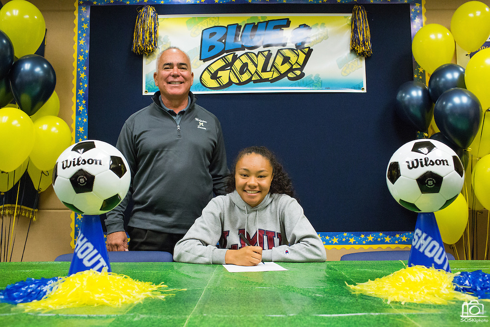 Sarina Bolden and Milpitas High School Soccer coach Michael Tomlin (left) pose with a duplicate National Letter of Intent to play soccer at the Loyola Marymount University during the NCAA National Signing Day event at Milpitas High School in Milpitas, California, on February 4, 2015. (Stan Olszewski/SOSKIphoto)