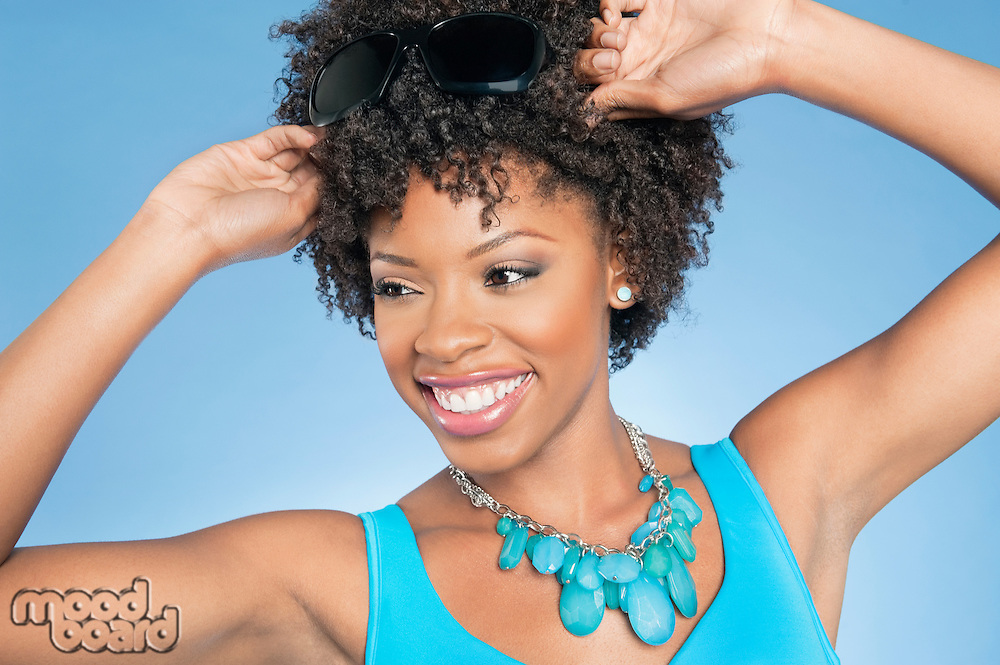 Happy African American woman adjusting sunglasses while looking away over colored background