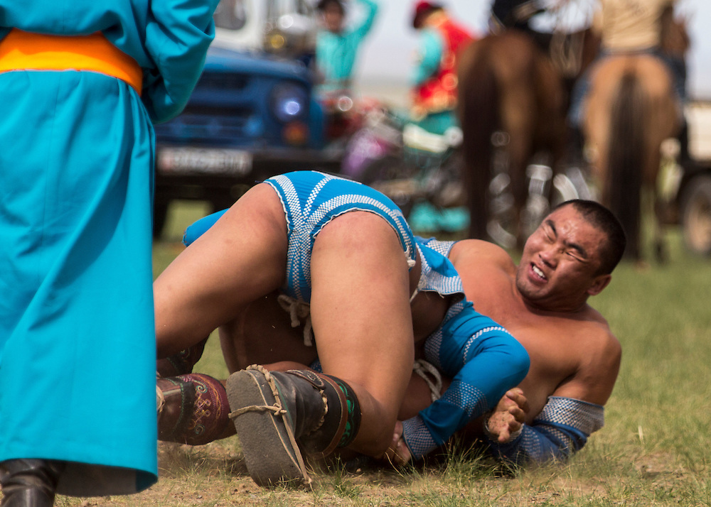 Two men compete during the final round of the wrestling competition of the Naadam Festival at the Three Camel Lodge in the Gobi Desert of Mongolia on July 31, 2012. Wrestling is one of the ?Three Manly Sports? practiced during the Naadam Festival. © 2012 Tom Turner Photography