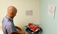 Michael Grabinski, two weeks old (R) is weighed by Dr. David Brumbaugh after being weighed at The Children's Hospital in Aurora, Colorado August 23, 2010 during a research study on obesity in infants. The overall theme of the study is to understand the continuum of growth that starts really at conception, and to understand if the earliest phases of growth impacts later risk for obesity.   REUTERS/Rick Wilking (UNITED STATES)