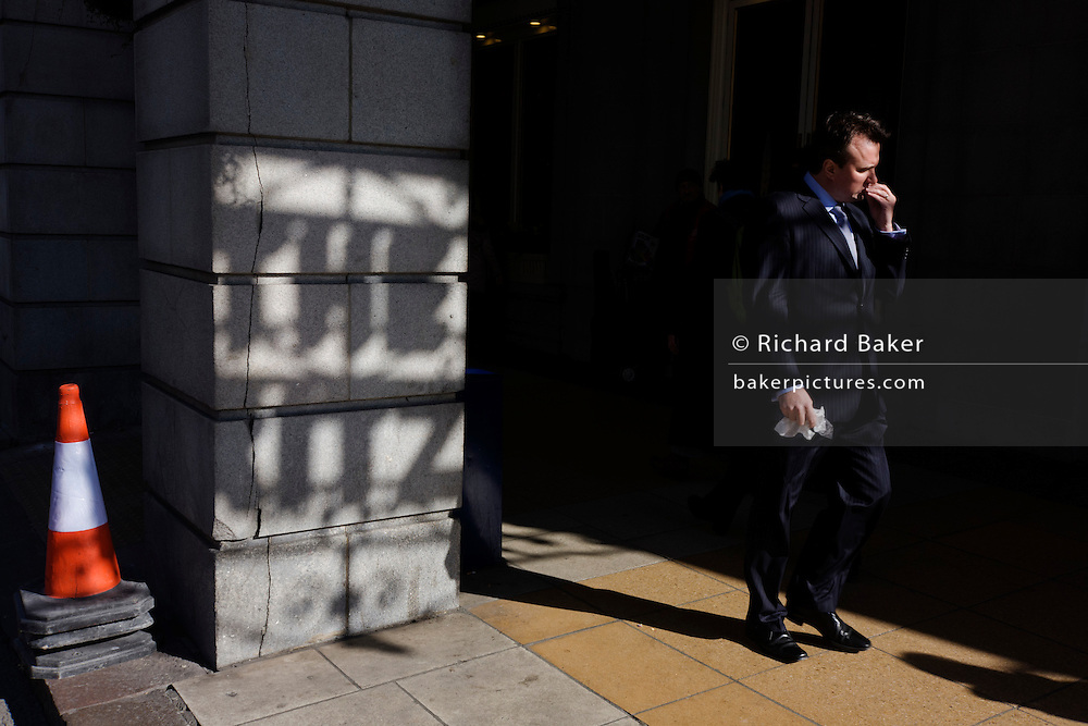 Lunchtime passer-by walks past a shadow of the Ritz Hotel sign, showing on a pillar outside the famous London landmark.