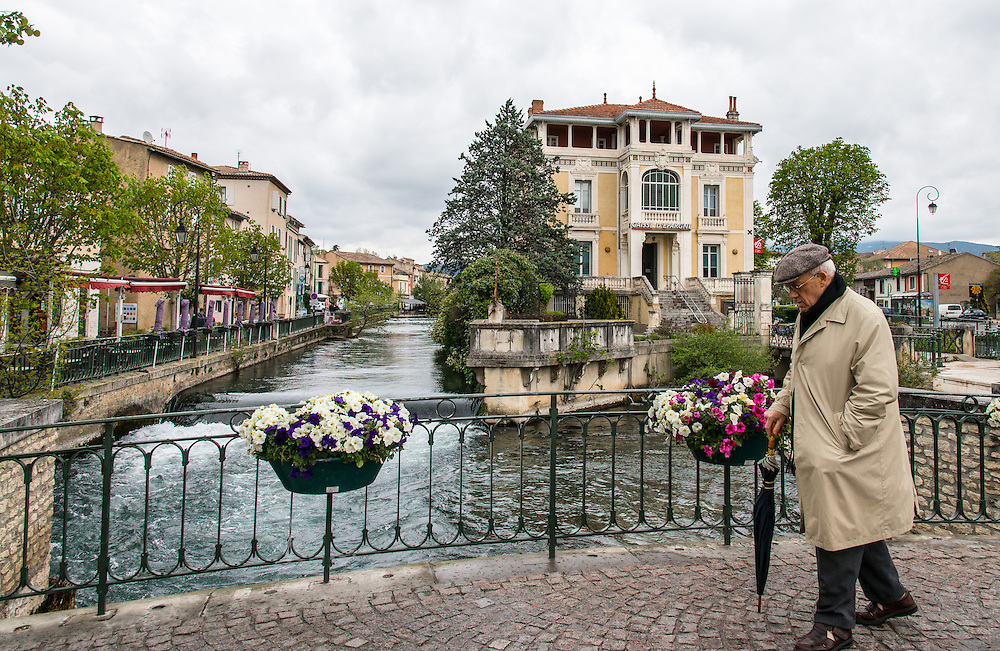 """The sombre appearance of the old man seems to match the cloudy day's atmosphere on L'Isle-sur-la-Sorgue  (the isle on the river Sorgue). Also known as  the """"Venice of Frnace"""",  several parts of the city are separated by the river's  tributes, making it a very picturesque location."""