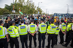 London, UK. 6 September, 2019. Metropolitan Police officers monitor climate activists, including some locked together using arm tubes in front of the cordon, taking part in Stop The Arms Fair protests outside ExCel London on the fifth day of a week-long carnival of resistance against DSEI, the world's largest arms fair. The road remained blocked for several hours. The fifth day of protests was themed as Stop The Arms Fair: Stop Climate Change in order to highlight links between the fossil fuel and arms industries.
