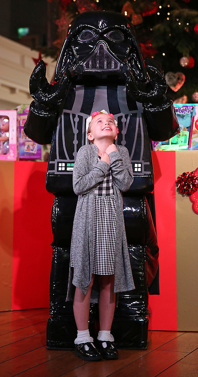 © Licensed to London News Pictures. 04/11/2015. London, UK. Nine year old Isabelle stands with a Star Wars Darth Vader character at the Dream Toys Christmas event. Photo credit: Peter Macdiarmid/LNP