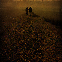 Two figures walking along a beach into the distance on a cold day