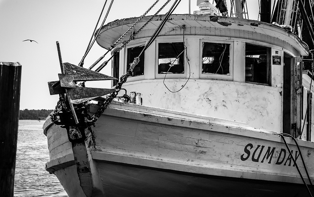 A local shrimp boat, the Sum Day, is docked behind the historic Calabash resturant row.  She is one of the older boats in the local fleet, her age reflects much of the character that makes this image an interesting composition.