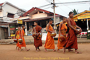A group of Buddhist monks walk down the main street holding their bowls during this daily early morning street ritual in Vang Vieng, Laos.