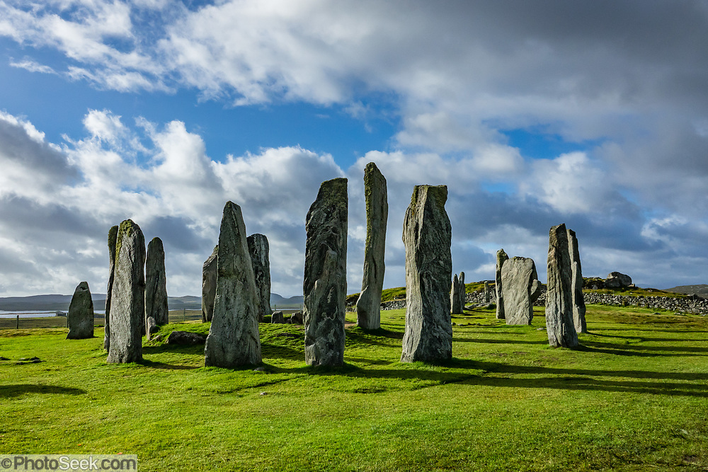 """Erected 4600 years ago, the Callanish Standing Stones are one of the most spectacular megalithic monuments in Scotland. The main site known as """"Callanish I"""" forms a cross with a central stone circle erected circa 2900-2600 BC. More lines of stones were added by 2000 BC (the close of the Neolithic era), and it become a focus for rituals during the Bronze Age. From 1500-1000 BC, farmers emptied the burials and ploughed the area. After from 800 BC, peat accumulated 1.5 meters deep and buried the stones until removed in 1857. Visit this spectacular ancient site near the village of Callanish (Gaelic: Calanais), on the Isle of Lewis, Outer Hebrides (Western Isles), Scotland, United Kingdom, Europe."""