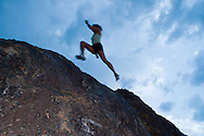 A young woman leaping through the air while trail running on the Boulder Vally Ranch trail near Boulder, Colorado