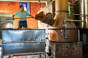 A worker loads a batch of fermented blue agave mash into the still at the Casa Siete Leguas, El Centenario tequila distillery in Atotonilco de Alto, Jalisco, Mexico. After being crushed by a stone mill the agave fibers are mixed with spring water and fermented before being distilled into tequila and then aged in barrels. The Seven Leagues tequila distillery is the oldest family owned distillery producing authentic handcrafted tequila using traditional methods.