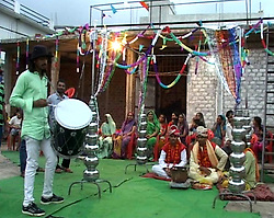 August 8, 2017 - Indore, MADHYA PRADESH, INDIA - MADHYA PRADESH, INDIA - AUGUST, 03, 2017: Local artist beats a drum during the marriage ceremony of Sakaram Ahirwar, 35, (right) and Rakesh Ahirwar, 32, (second from right) dressed in their traditional wedding attire, during their marriage ceremony in Indore, a city in Madhya Pradesh, India.....The two men married each other in the traditional Hindu way in front of their friends and family, as a gesture to bring good rain to Indore from Indradev, the Hindu god of lightning, thunder, storms, rains and river flows. The gala event was attended by around 300 people, including the wives and five children of both Sakaram and Rakesh. The event saw attendees relishing excessive amounts of food and dancing.....Pictures supplied by: Cover Asia Press (Credit Image: © Cover Asia Press/Cover Asia via ZUMA Press)