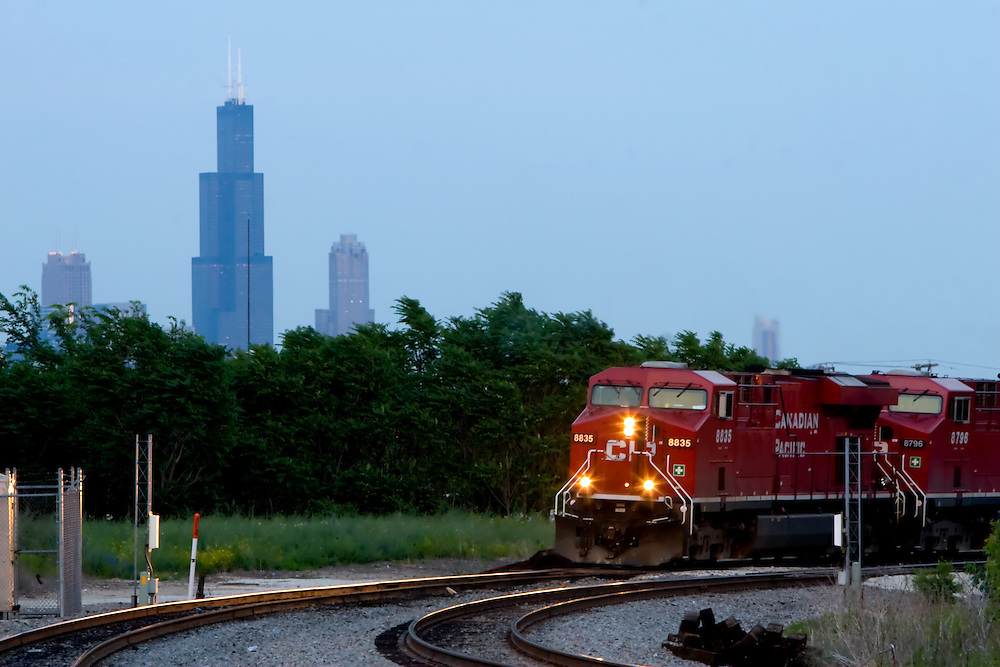 A Canadian Pacific freight train rounds a curve in Chicago, IL, with the Sears Tower in the background.