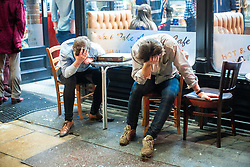 "© Licensed to London News Pictures . 22/12/2018 . Manchester , UK . Two men with a pizza sit outside a takeaway on Deansgate , both clutching their heads in the hands . Revellers out in Manchester City Centre overnight during "" Mad Friday "" , named for historically being one of the busiest nights of the year for the emergency services in the UK . Photo credit : Joel Goodman/LNP"