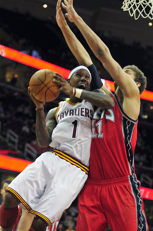 March 23, 2010; Cleveland, OH, USA; Cleveland Cavaliers point guard Daniel Gibson (1) tries to shoot over New Jersey Nets center Brook Lopez (11) during overtime at Quicken Loans Arena. The Nets beat the Cavaliers 98-94 in overtime. Mandatory Credit: Jason Miller-US PRESSWIRE
