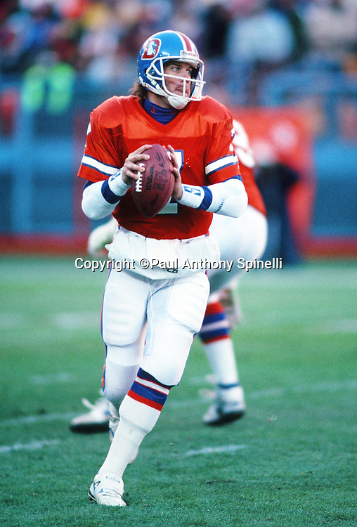Denver Broncos quarterback John Elway (7) rolls out while looking to pass during the NFL football game against the Los Angeles Raiders on Dec. 2, 1990 in Denver. The Raiders won the game 23-20. (©Paul Anthony Spinelli)